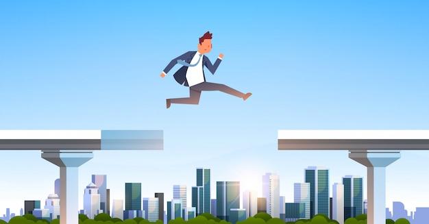 Empresario saltando sobre brecha Vector Premium