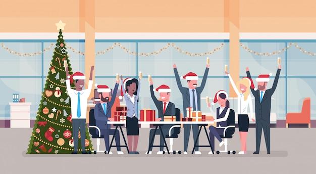 Equipo de negocios levantó las manos en la oficina moderna decorado abeto feliz año nuevo feliz celebración de navidad concepto horizontal Vector Premium