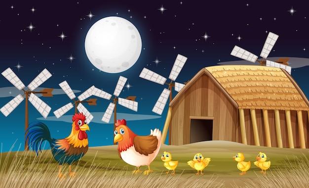 Escena de la granja con granero y molino de viento y pollo por la noche. vector gratuito