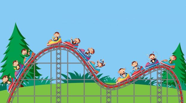 Escena con monos montando en montaña rusa en el parque vector gratuito