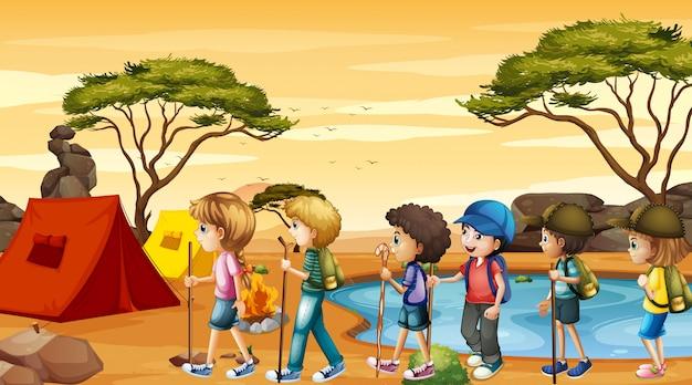 Escena con niños caminando y acampando vector gratuito