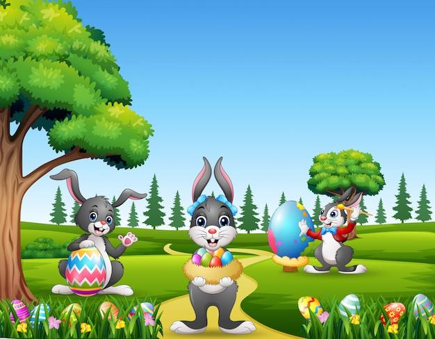 Felices conejitos de pascua sosteniendo y pintando huevos Vector Premium