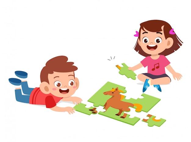 Felices los niños lindos juegan resolver rompecabezas juntos Vector Premium
