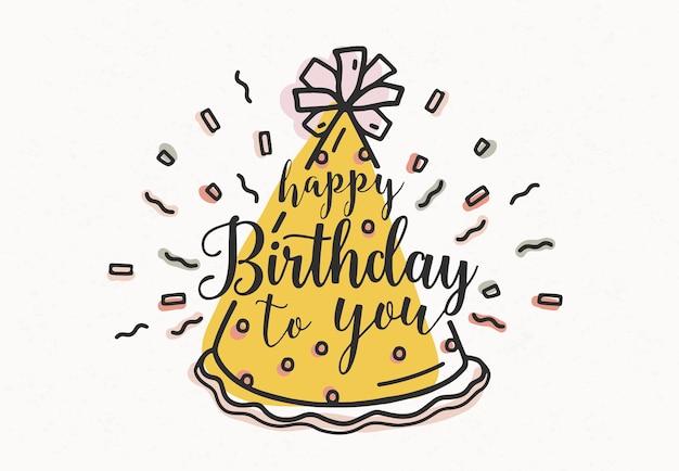 Feliz cumpleaños a ti, escrito a mano con letra cursiva y decorado con gorro de fiesta de cono y confeti Vector Premium