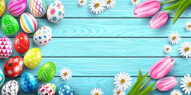 Feliz plantilla de pascua con coloridos huevos de pascua y flores en la mesa de madera Vector Premium
