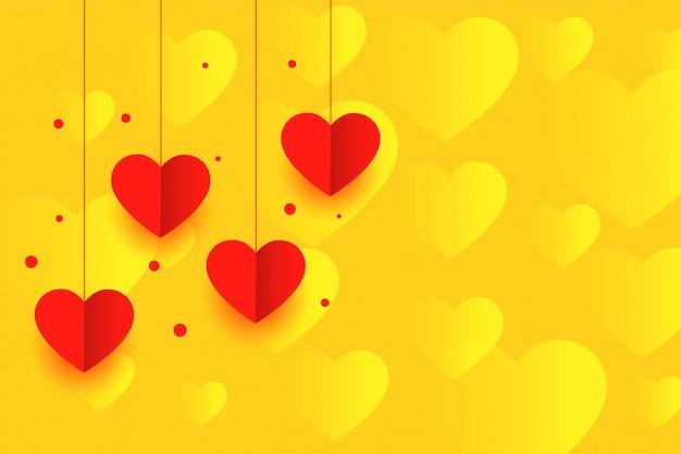 Fondo amarillo con fondo de corazones de papel colgante rojo vector gratuito