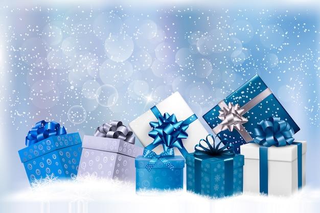 Fondo de navidad azul con cajas de regalo y copos de nieve. Vector Premium