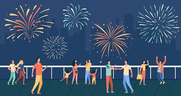 Gente feliz celebrando en la calle de la ciudad y viendo la ilustración plana de fuegos artificiales. vector gratuito