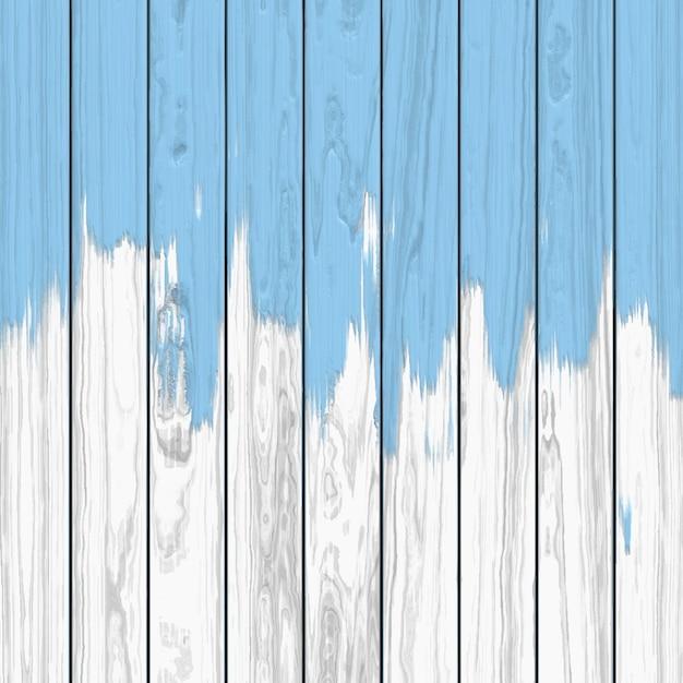 Goteo de pintura azul sobre un fondo de madera blanca Vector Gratis