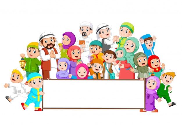 Una gran familia musulmana se reúne cerca del marco en blanco. Vector Premium