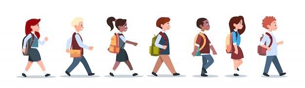 Grupo de alumnos mezcla raza caminar escuela niños aislado diversos pequeños estudiantes de primaria Vector Premium
