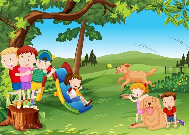 Grupo de niños y perros jugando en el parque. Vector Premium