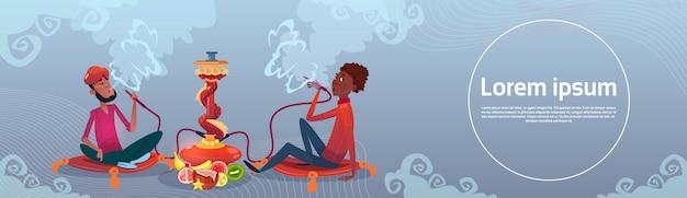 Hombre árabe fumando pipa de narguile sentado en el suelo Vector Premium