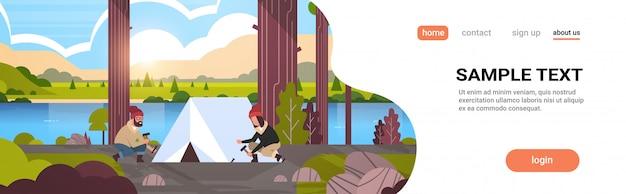 Hombre mujer excursionistas campistas instalando una carpa preparándose para acampar senderismo concepto amanecer paisaje naturaleza río montañas Vector Premium
