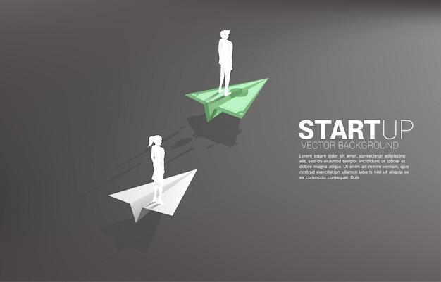 El hombre de negocios y la empresaria que se colocan en el avión de papel del origami del billete de banco del dinero se mueven más rápido que el blanco. concepto de negocio de carril rápido para mover y poner en marcha. Vector Premium