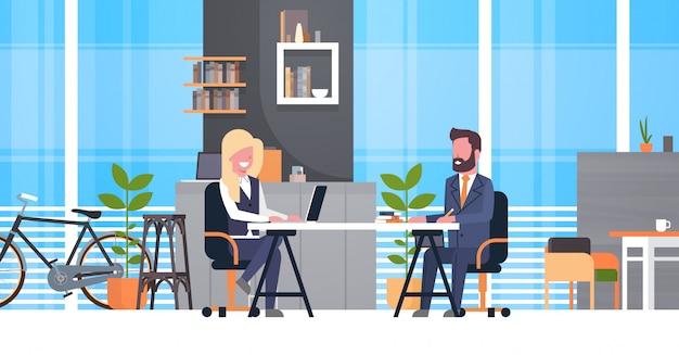 Hombre de negocios en entrevista de trabajo con el gerente femenino de hr, dos hombres de negocios que se sientan en el escritorio en la reunión adentro Vector Premium