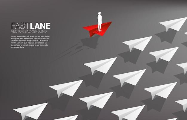 El hombre de negocios que se coloca en el aeroplano de papel rojo del origami se mueve más rápido que el grupo de blancos. Vector Premium