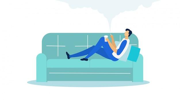 Hombre que miente en el sofá que sostiene la taza y que fuma plano. Vector Premium