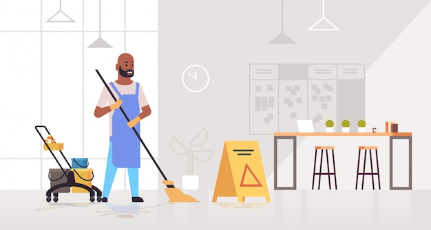 Hombre trapeando el piso limpiador masculino en concepto de servicio de limpieza uniforme conserje cerca del carrito con suministros creativo centro de trabajo colaborativo interior de la oficina horizontal de longitud completa Vector Premium