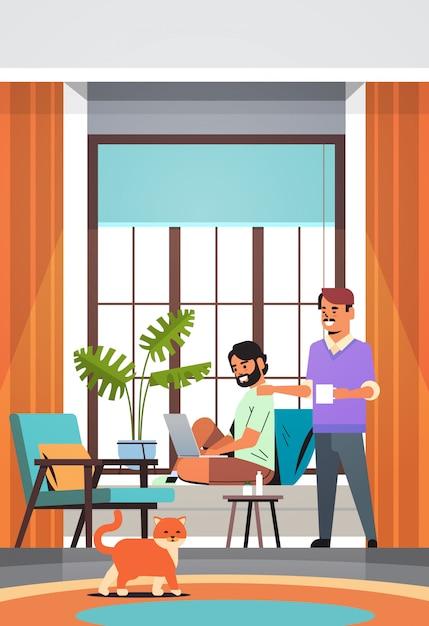 Hombres pareja usando laptop tomando café pasando tiempo juntos durante la cuarentena de coronavirus Vector Premium