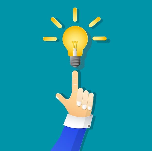 Icono de bombilla de luz amarilla y hombre de negocios de la mano en el arte de papel Vector Premium