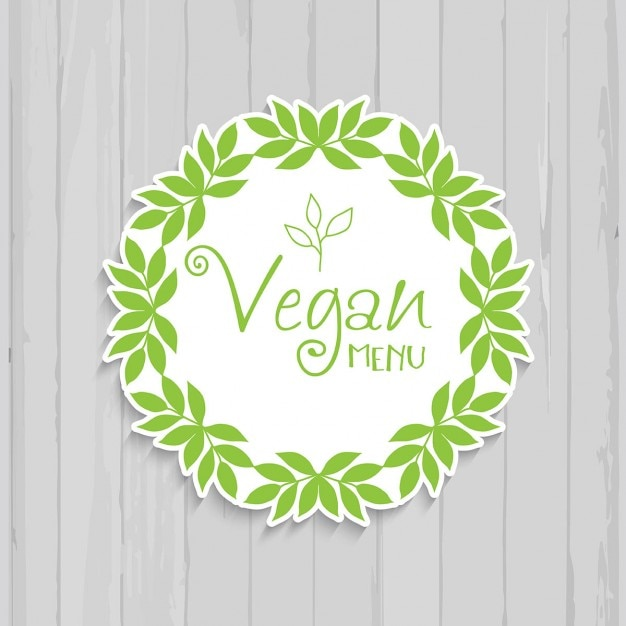 Insignia vegana decorativa en un fondo de madera vector gratuito