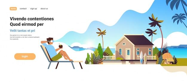 Joven use gafas digitales sentado tumbona visión de realidad virtual villa casa tropical playa verano vacaciones concepto plana Vector Premium