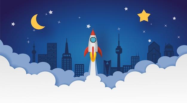 Lanzamiento de un cohete al cielo nocturno sobre la ciudad con luna y estrellas. diseño vectorial en corte de papel. Vector Premium
