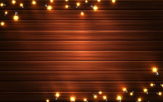 Luces de navidad. guirnaldas sobre fondo de madera Vector Premium