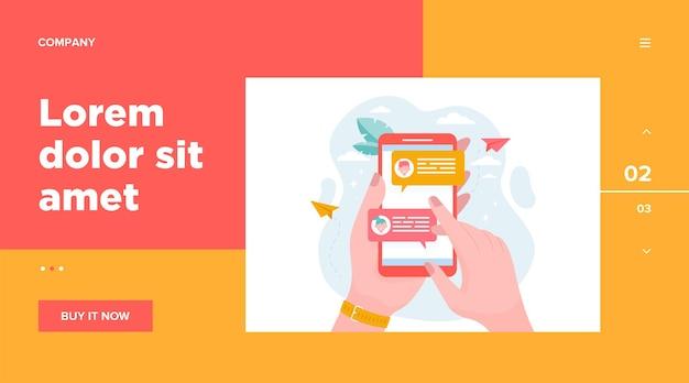 Mano que sostiene el teléfono móvil con la ilustración de vector plano de mensajes en línea. pantalla de teléfono inteligente moderno con chat. concepto de comunicación y conversación vector gratuito