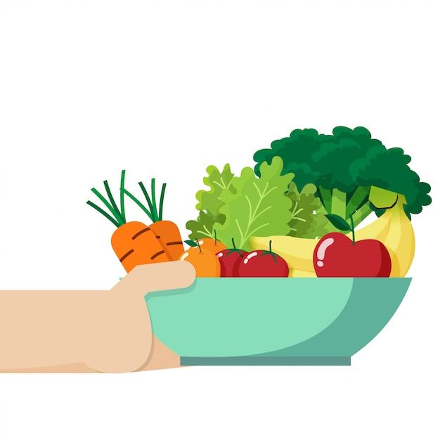 Mano sosteniendo un bol lleno de verduras y frutas frescas Vector Premium