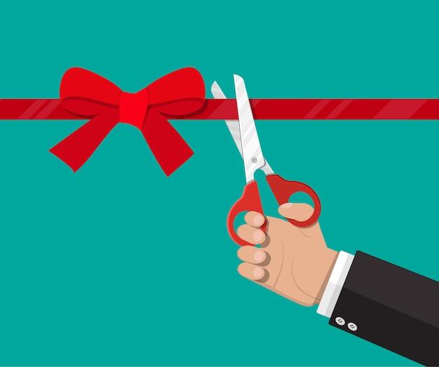 Mano con tijeras corta cinta roja Vector Premium