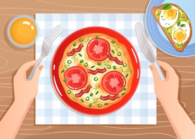 Manos con cubiertos sobre huevos revueltos con tomate y tocino en mesa de madera plana vector gratuito