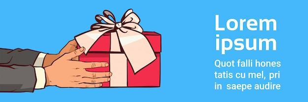 Manos sosteniendo la caja de regalo roja con lazo de cinta en la plantilla Vector Premium