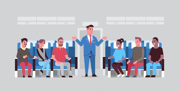 Mayordomo explicando las instrucciones para los pasajeros de la raza mixta azafata en uniforme haciendo gestos con las manos mostrando salidas de emergencia concepto de demostración de seguridad tablero de avión horizontal Vector Premium
