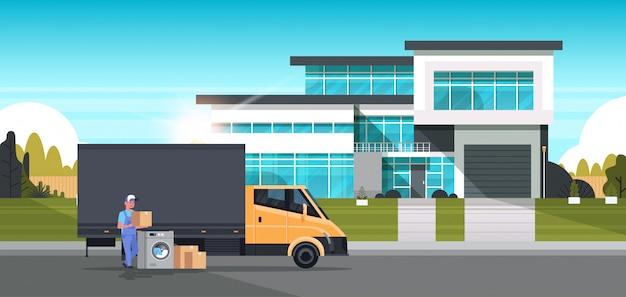 Mensajero hombre cerca de camión de reparto con cajas de cartón lavadora electrodomésticos tienda de bienes compra distribución concepto casa cabaña exterior Vector Premium