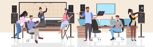 Mezclar las personas que realizan en el estudio de grabación hombres mujeres usando aparatos digitales comunicación de red social de longitud completa horizontal Vector Premium
