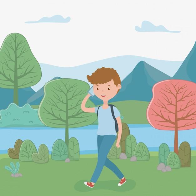 Muchacho joven que camina usando smartphone en el parque vector gratuito
