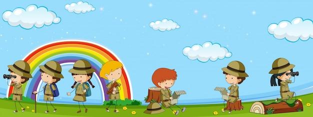 Muchos niños en uniforme de scout se divierten en el parque vector gratuito