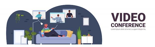 Mujer chateando con amigos de raza mixta durante la videollamada personas que tienen conferencia en línea reunión comunicación concepto sala de estar interior horizontal longitud completa copia espacio ilustración Vector Premium