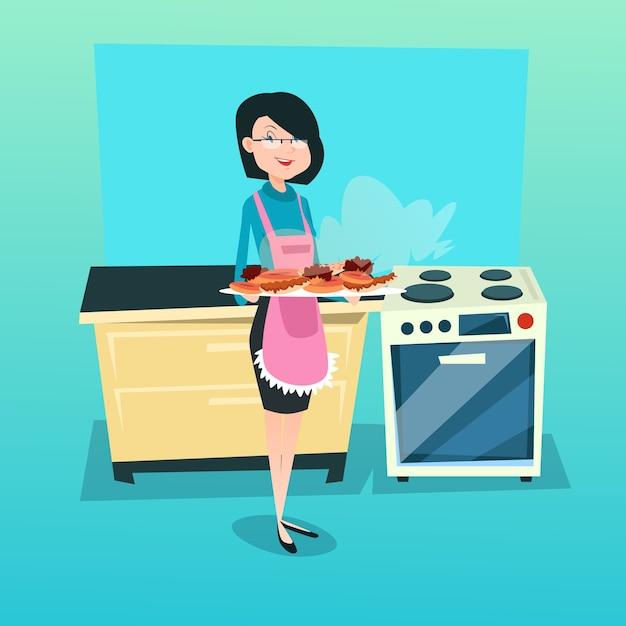 Mujer en cocina sosteniendo la bandeja con tortas galletas Vector Premium