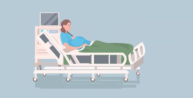 Mujer embarazada acostada en la cama de hospital antes del parto concepto de embarazo de maternidad integral Vector Premium