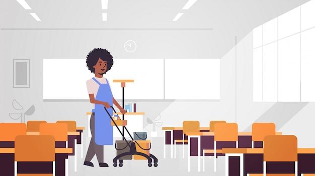 Mujer empujando el carrito con suministros conserje limpiador femenino en concepto de servicio de limpieza uniforme interior moderno aula de la escuela horizontal de longitud completa Vector Premium