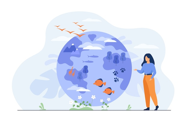 Mujer feliz de pie y apuntando en globo con ilustración plana de diversidad de flora y fauna. vector gratuito