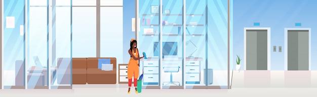 Mujer limpiador limpiando la pared de vidrio mujer afroamericana conserje utilizando tela de polvo concepto de servicio de limpieza creativo lugar de trabajo oficina interior plana horizontal de longitud completa Vector Premium