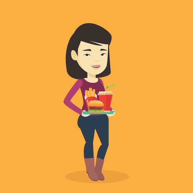 Mujer que sostiene la bandeja llena de comida rápida. Vector Premium