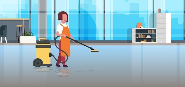 Mujer sosteniendo profesional aspiradora limpiador femenino conserje en servicio de limpieza uniforme cuidado del piso moderno co-working interior de oficina Vector Premium
