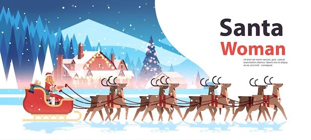 Mujer en traje de santa claus montando trineo con renos feliz año nuevo feliz navidad concepto de celebración navideña paisaje de invierno fondo espacio de copia horizontal ilustración vectorial Vector Premium