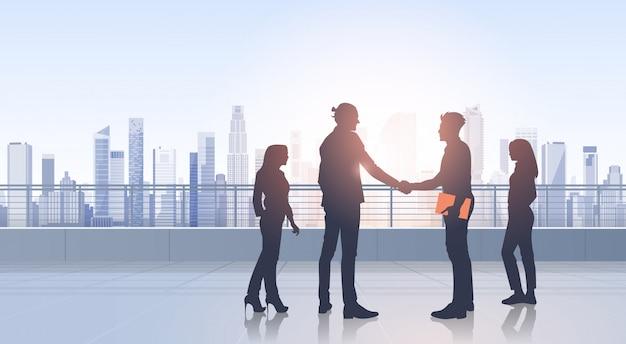 Negocio grupo de personas reunión acuerdo mano agitar siluetas moderno vista de la ciudad edificio de oficinas Vector Premium