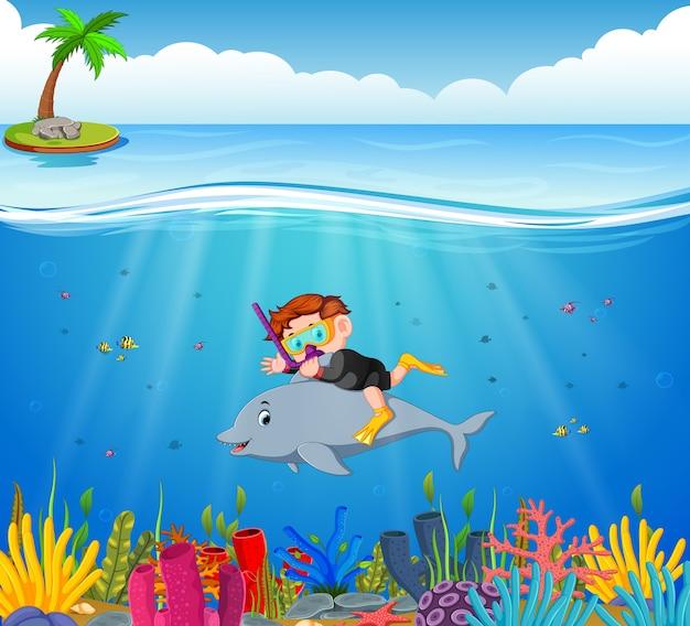 Niño De Dibujos Animados De Buceo En El Mar Con Delfines Vector Premium
